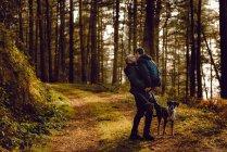 Coppia omosessuale abbracciare e baciare vicino cane sulla strada nella foresta nella giornata di sole — Foto stock