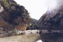 Обратный вид женщины с рюкзаком на берегу горной реки возле скальной горы — стоковое фото