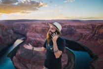 Homem de chapéu falando no telefone celular enquanto está de pé contra o magnífico desfiladeiro e rio durante o pôr do sol na Costa Oeste dos EUA — Fotografia de Stock
