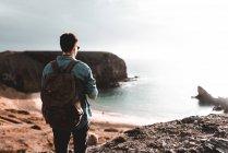 Vista posteriore del giovane turista in piedi sulla scogliera vicino al mare a Lanzarote, Isole Canarie, Spagna — Foto stock