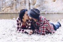 Вид сбоку на молодую пару, лежащую и целующуюся на скальном берегу горной реки возле скалы — стоковое фото