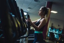 Pretty strong woman on exercise machine — Stock Photo