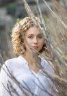 Giovane donna affascinante guardando la fotocamera vicino rami secchi di arbusto su sfondo sfocato — Foto stock
