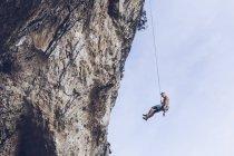 Da sotto scalatore appeso su corda su ruvida scogliera contro cielo blu — Foto stock