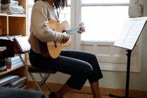 Mulher negra tocando guitarra durante o ensaio em estúdio de gravação — Fotografia de Stock