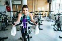 Femme de sourire dans des vêtements de sport avec la bouteille de l'eau et de la serviette regardant l'appareil-photo tout en s'asseyant sur la machine d'exercice dans la gymnastique moderne — Photo de stock