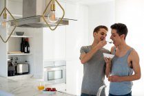 Affectionate gay couple having healthy breakfast at home in the kitchen — Stock Photo