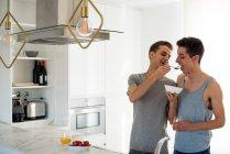 Ласковая гей-пара, завтракающая дома на кухне — стоковое фото