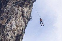 Dal basso scalatore irriconoscibile appeso alla corda su una ruvida scogliera contro il cielo blu — Foto stock