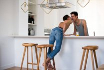 Affectionate sensual gay couple kissing at home in the kitchen — Stock Photo