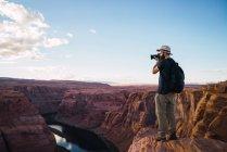 Vue latérale du gars avec sac à dos en utilisant un appareil photo pour prendre des photos du magnifique canyon et de la rivière calme sur la côte ouest des États-Unis — Photo de stock
