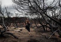 Молода балерина в чорному зносу з витягнутим руки позують між сухим лісом — стокове фото