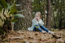 Positive little girl sitting near tree in forest on blurred background — Stock Photo