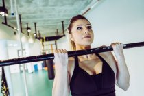 Strong woman doing pull ups in gym — Stock Photo
