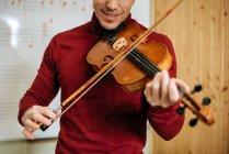 Jovem tocando violino com placa de escrita em segundo plano no estúdio de música — Fotografia de Stock