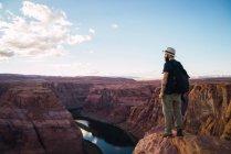 Vue latérale du gars avec sac à dos tenant appareil photo à beau canyon et rivière calme par une journée ensoleillée sur la côte ouest des États-Unis — Photo de stock