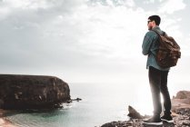 Young male tourist standing on cliff near sea in Lanzarote, Canary Islands, Spain — Stock Photo