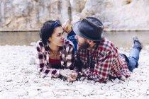 Вид сбоку на молодую пару, лежащую на скалистом берегу горной реки возле скалы — стоковое фото