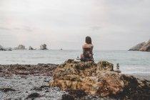 Вид сзади на молодую женщину, сидящую на скале на берегу моря и смотрящую на вид — стоковое фото