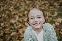 Портрет позитивной девочки, смотрящей в камеру на размытом фоне в природе — стоковое фото