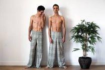 Elegante sin camisa pareja gay modelos de pie sobre un fondo blanco - foto de stock