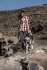 Smiling young woman walking with husky on deserted land in Tenerife, Canary Islands, Spain — Stock Photo