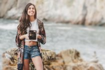 Smiling young woman holding camera on sea coast — Stock Photo
