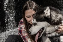 Cheerful young woman embracing husky in front of rock — Stock Photo