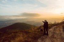 Casal homossexual de pé com o cão na rota em montanhas ao pôr do sol — Fotografia de Stock