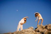 Junge geheimnisvolle Frauen mit erhobenen Händen posieren auf Felsen in der Nähe von Hügeln und blauem Himmel mit Mond — Stockfoto