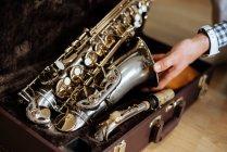 Mann mit Saxofon aus Koffer im Studio geschnappt — Stockfoto