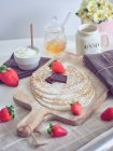 Petit déjeuner avec des crêpes et des fraises sur la table de cuisine avec des fleurs — Photo de stock