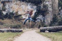 Случайный человек прыгает среди упавших стволов на сельской дороге против красивой скалы — стоковое фото