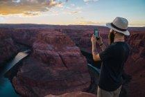 Bonito homem de chapéu tirando fotos enquanto estava de pé contra o magnífico desfiladeiro e rio durante o pôr do sol na Costa Oeste dos EUA — Fotografia de Stock