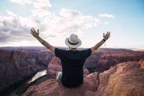Vue arrière de l'homme étirant les bras et admirant la vue du majestueux canyon contre un ciel bleu nuageux sur la côte ouest des États-Unis — Photo de stock