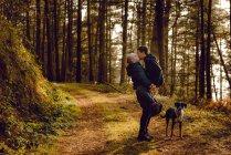 Coppia omosessuale abbracciando vicino cane sulla strada nella foresta nella giornata di sole — Foto stock