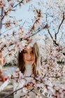 Young happy woman between trees in garden — Stock Photo