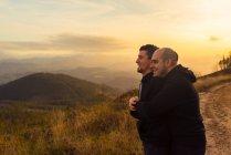Feliz pareja homosexual abrazando y disfrutando de la puesta de sol en la ruta en las montañas - foto de stock