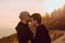 Felice coppia omosessuale abbracciare e baciare sul sentiero nella foresta nella giornata di sole — Foto stock
