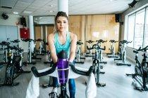 Femme avec la serviette et l'eau sur la machine d'exercice — Photo de stock