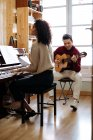 Side view of young black woman playing piano near man playing guitar in music studio — Stock Photo