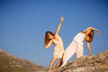 Mujeres jóvenes misteriosas con las manos levantadas posando en rocas cerca de la colina y el cielo azul con la luna - foto de stock