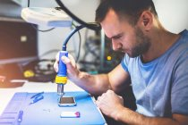 Focused repairing smartphone with solder at workplace — Stock Photo