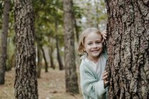 Positive child looking at camera behind tree in forest on blurred background — Stock Photo
