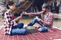 Vista laterale di uomo e donna in camicie a quadri giocare a carte sul plaid fare picnic sulla riva del lago in scogliere — Foto stock