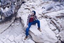 Dall'alto donna sorridente attraente che riposa su roccia su montagna — Foto stock