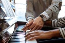 Mujer joven aprendiendo a tocar el piano cerca del profesor en el estudio de música - foto de stock