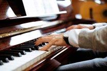 Seitenansicht eines Mannes, der in einem Musikstudio Klavier spielt — Stockfoto