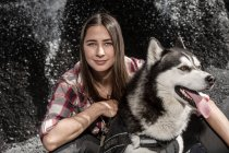 Smiling young woman embracing husky in front of rock — Stock Photo