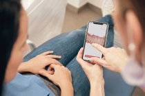 Female dentist demonstrating smartphone with teeth scan to woman in clinic — Stock Photo